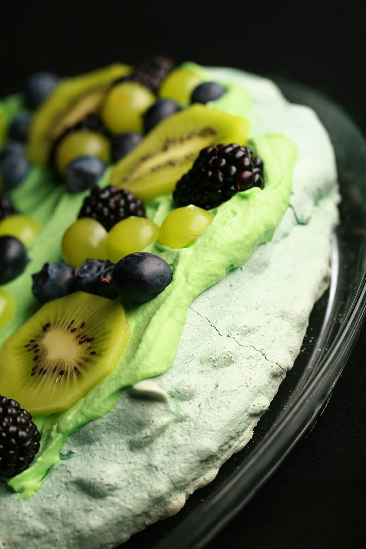 A blue meringue topped with green whipped cream, kiwi slices, green grapes, blueberries, and blackberries.