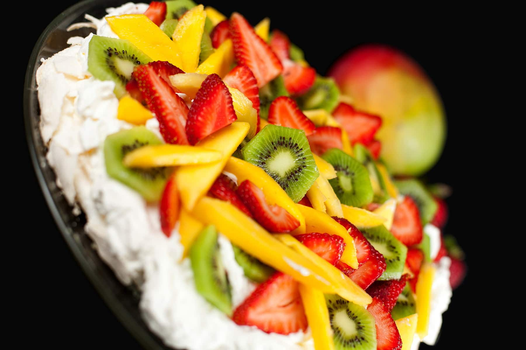 Close up view of a Pavlova: White meringue topped with whipped cream, strawberries, kiwi fruit, and mango slices.