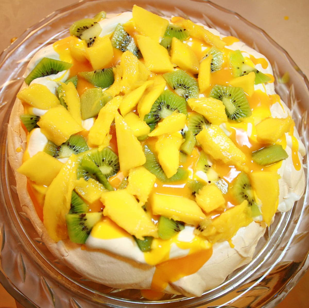 A roudn white meringue topped with whipped cream, mango slices, kiwi slices, and mango sauce.