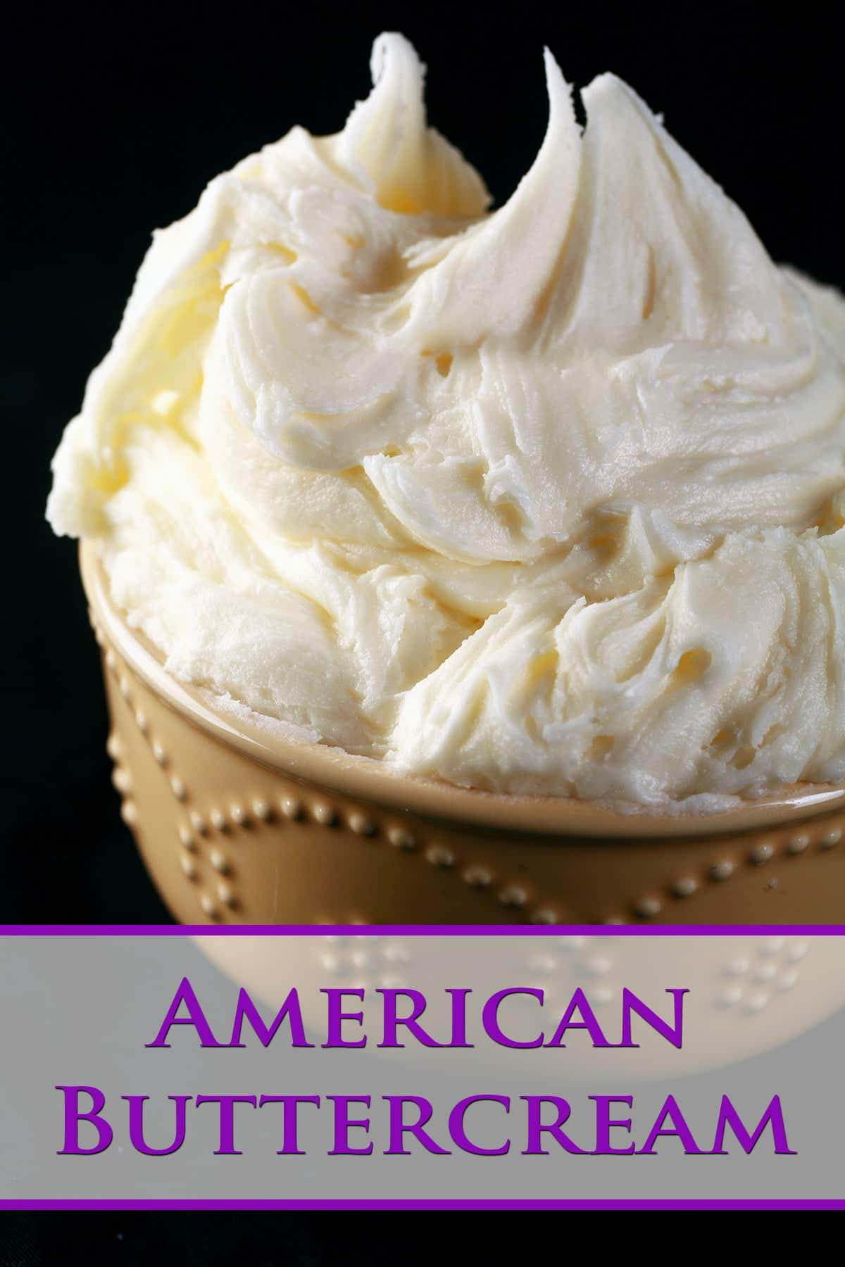 A bowl full of - and mounded high with - off white American Buttercream is shown in front of a black background.