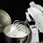 A white stand mixer is pictured against a black background. It's tilted up, showing the meringue in the bowl and on the whisk attachment.