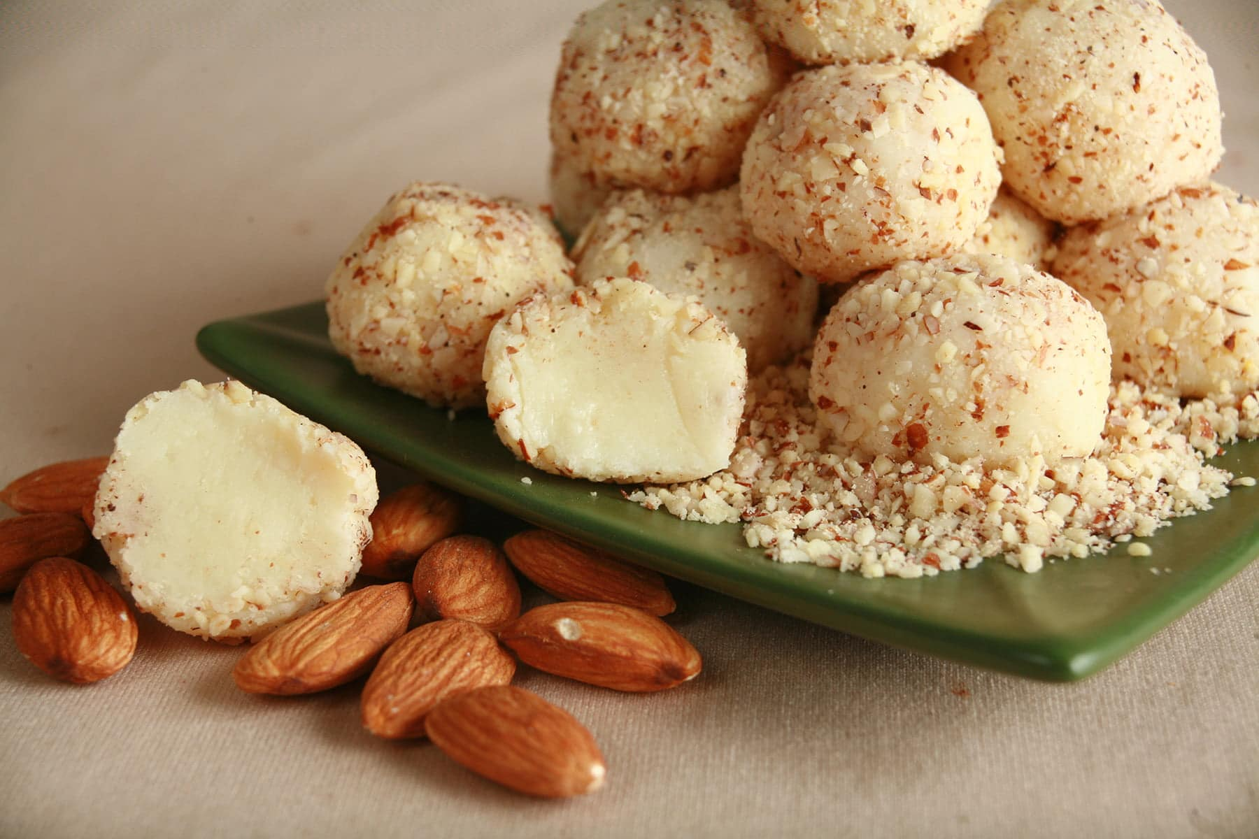 A close up view of a pile of white chocolate truffles, on a small green plate. The truffles are covered in finely chopped almonds, and there are a few whole almonds in the foreground.