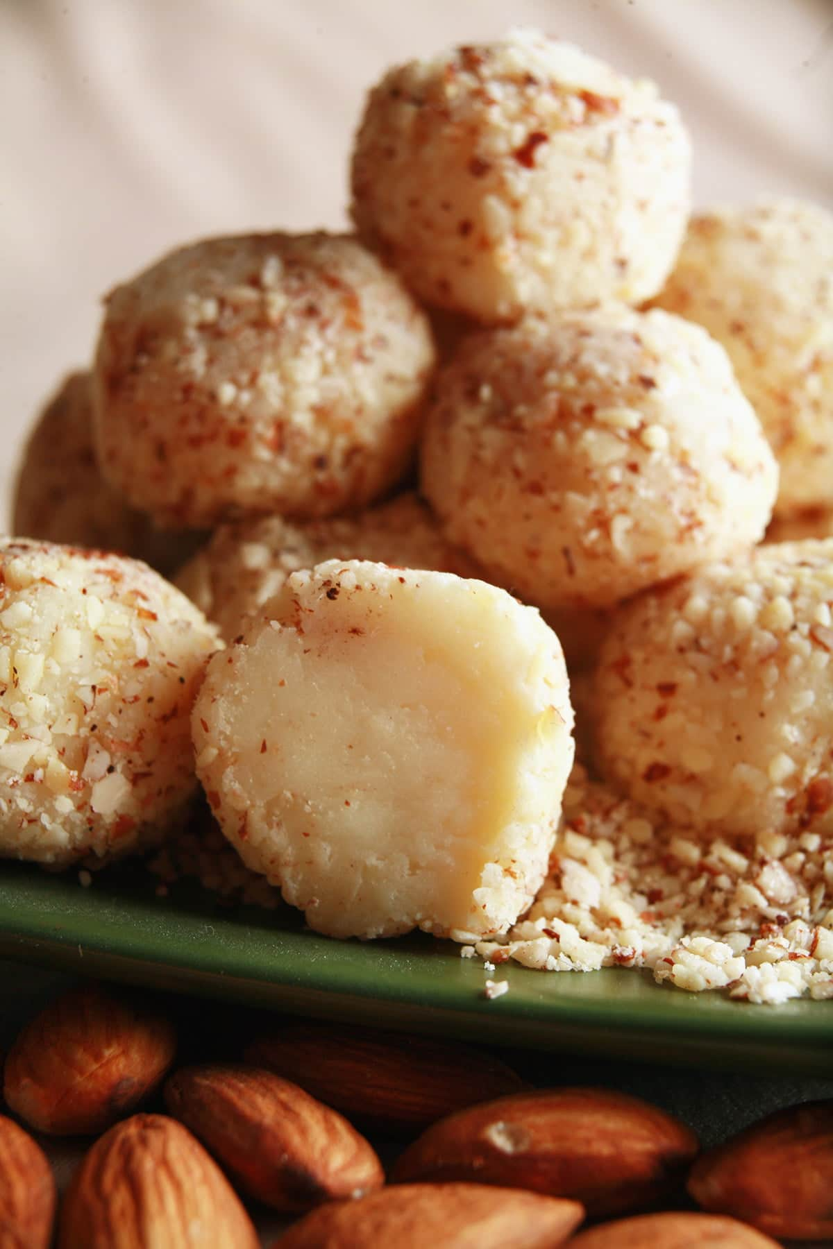 A close up view of a pile of white chocolate amaretto truffles, on a small green plate. The truffles are covered in finely chopped almonds, and there are a few whole almonds in the foreground.