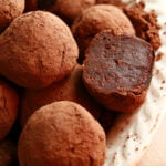 Close up view of a small white plate piled with homemade dark chocolate truffles.