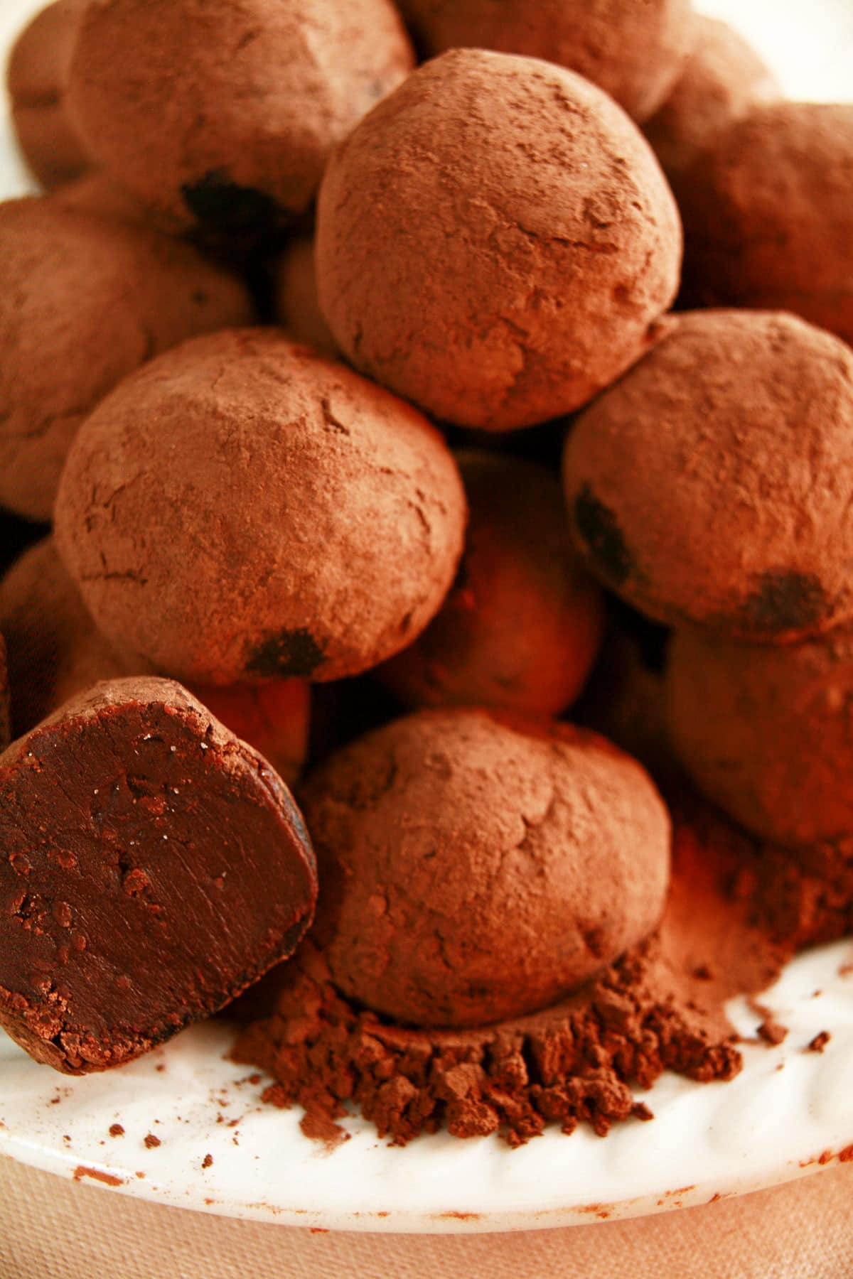 Close up view of a small white plate piled with homemade truffles.  They're made from dark chocolate, and are rolled in cocoa powder.