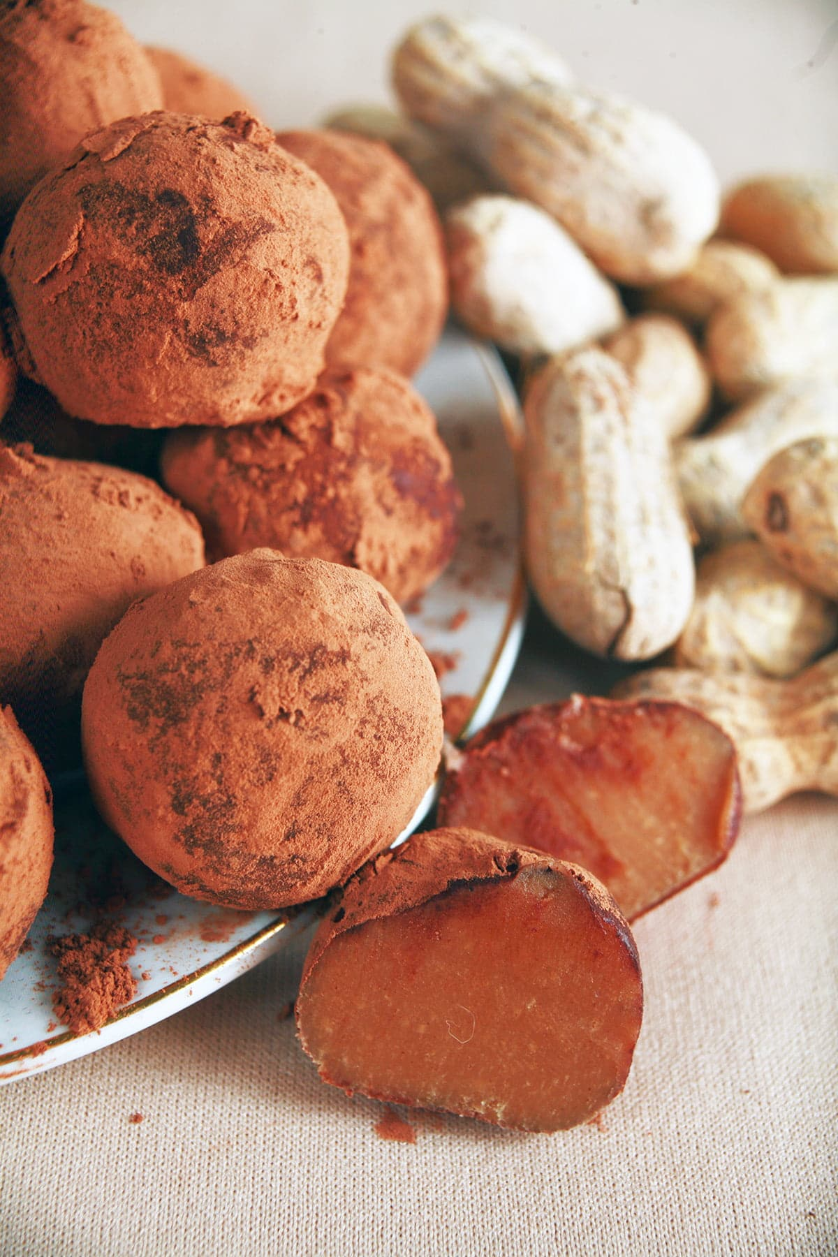 Several peanut butter chip truffles are spilling off a small plate, with whole peanuts in the shell on display behind them.