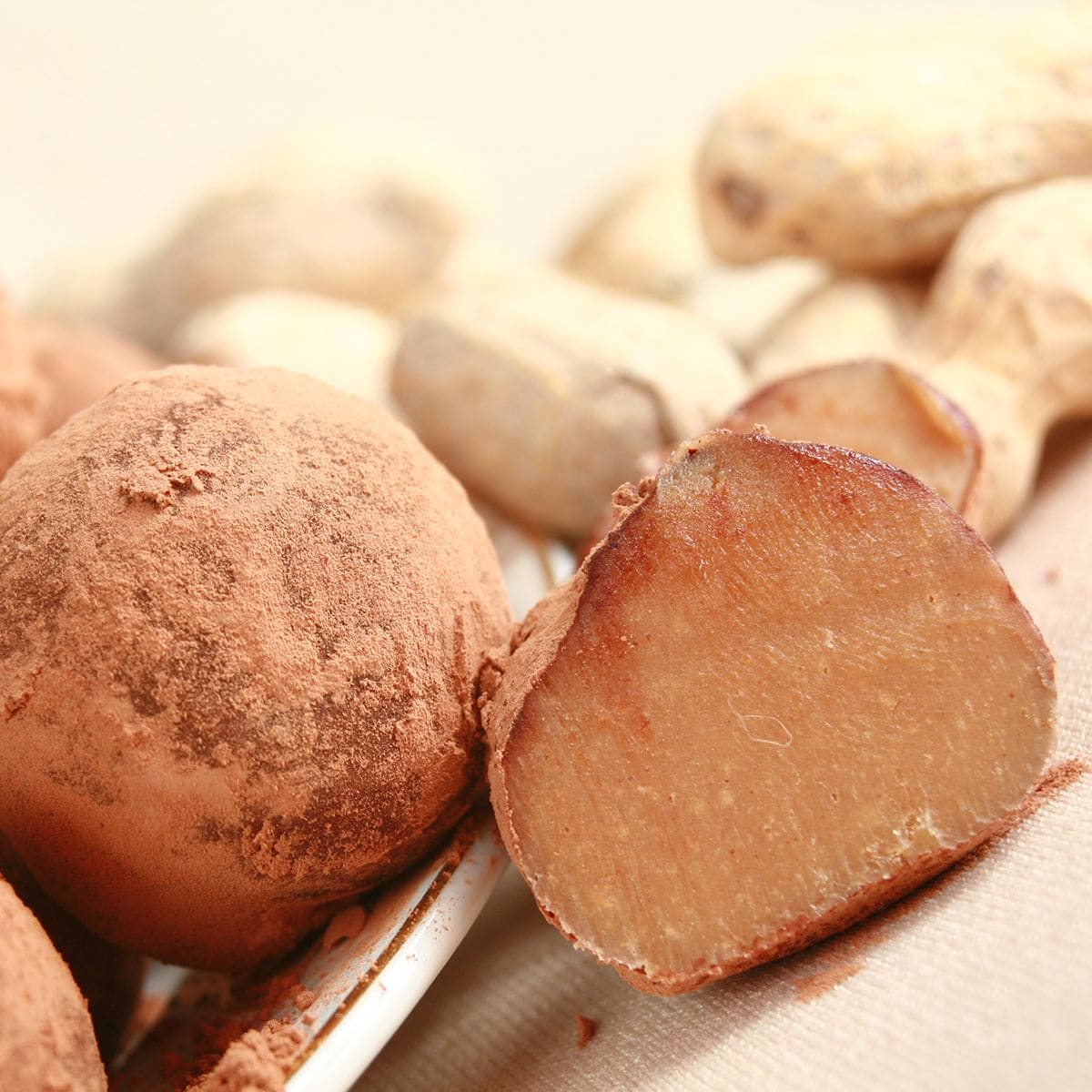 Several peanut butter coloured truffles - rolled in cocoa powder - are spilling off a small plate, with whole peanuts in the shell on display behind them.