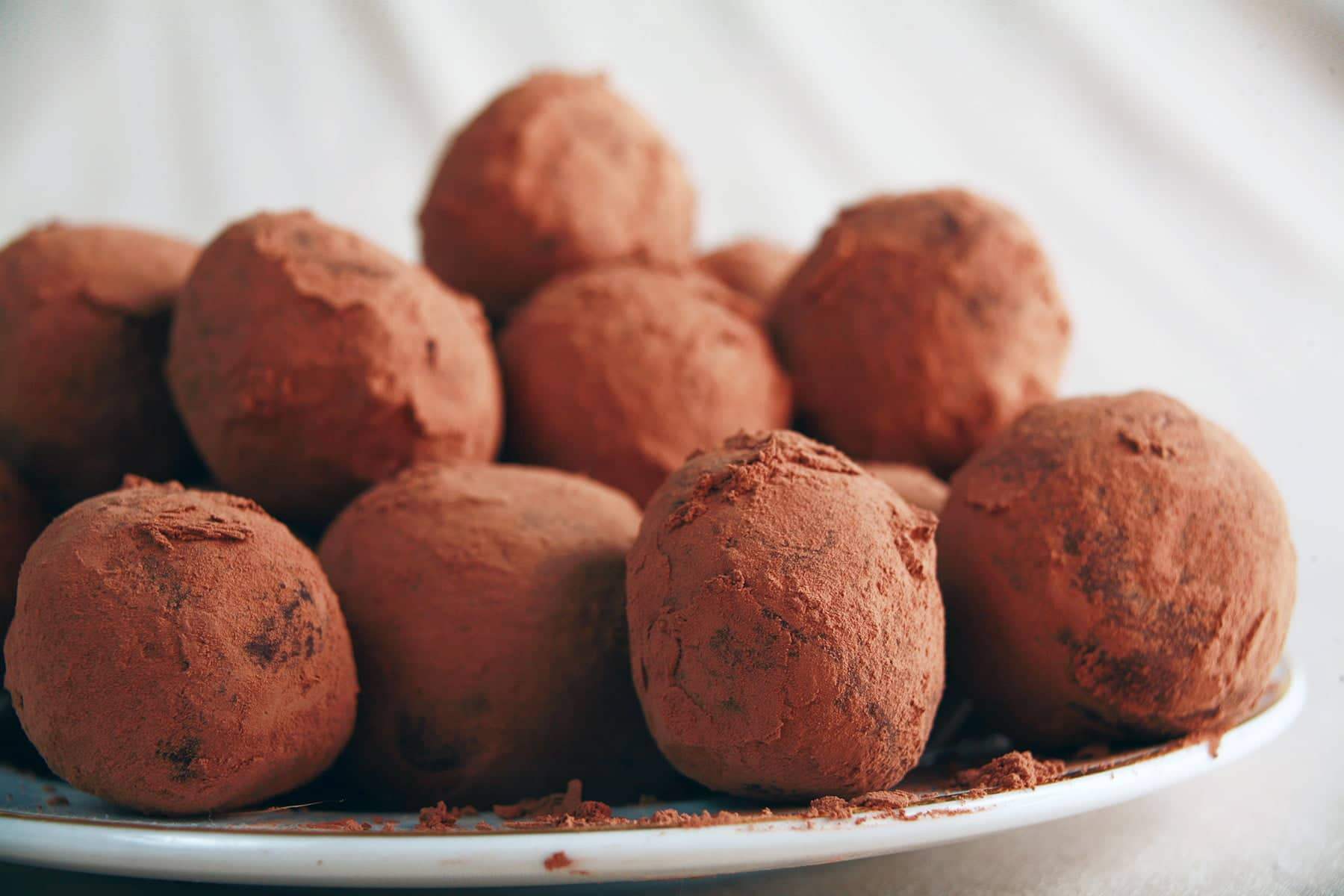 A close up view of a small white plate, piled high with sugar free chocolate chip truffles.