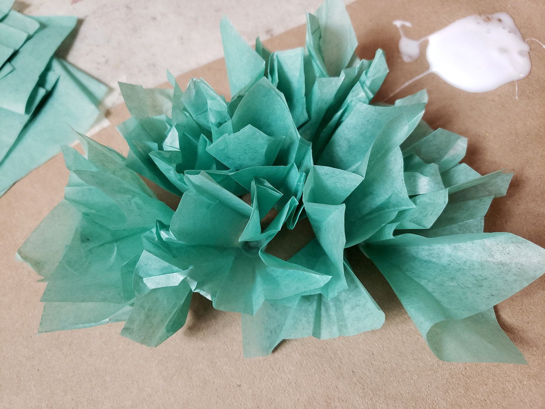 A group of light green tissue puffs on a brown paper background.