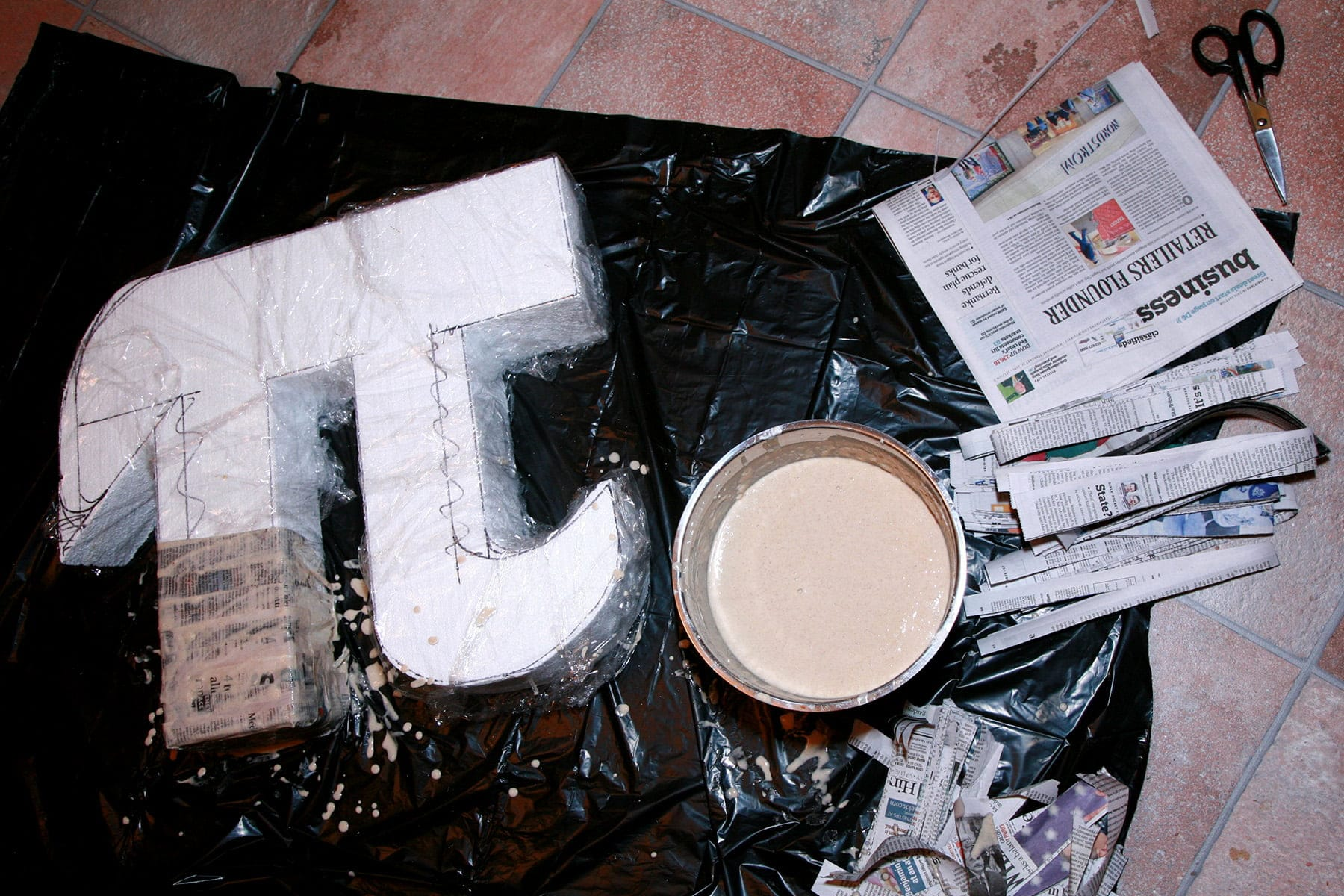 A large pi symbol shape - made of foam - is being covered in paper mache.