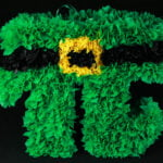 A bright green pi symbol-shaped pinata, against a black background.