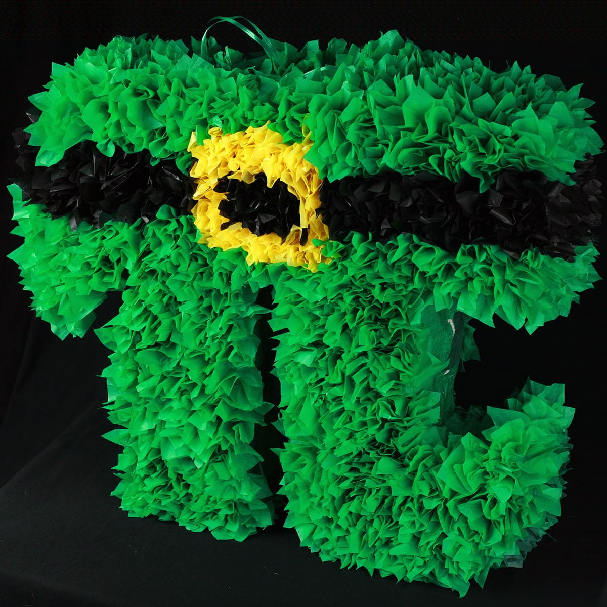 A bright green pi symbol-shaped pinata, against a black background.