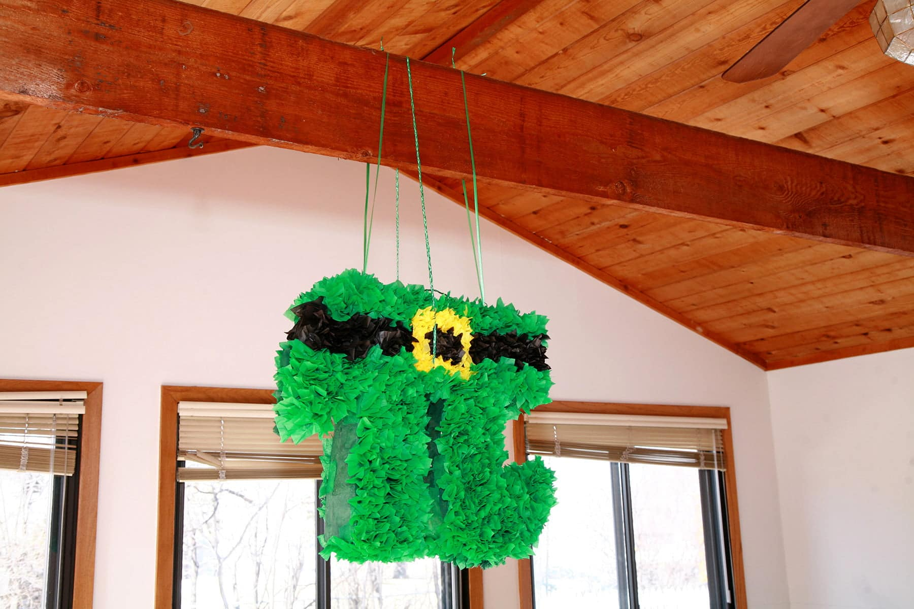 A bright green pi symbol shaped pinata is suspended from a wooden rafter.