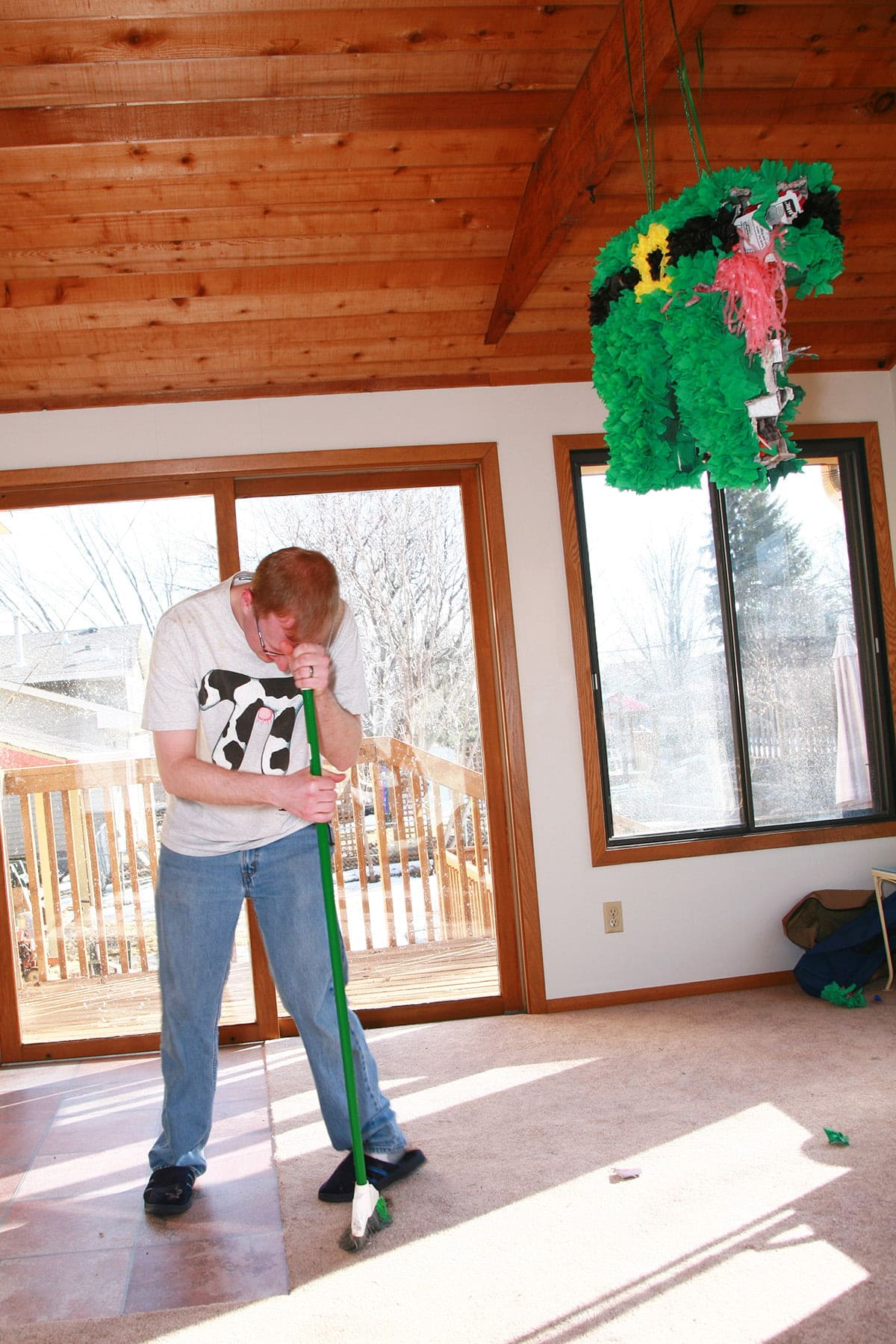 A young blond man wearing a t shirt with a white and black cow print pi symbol on it stoops over a broom, beneath a suspended pinata.