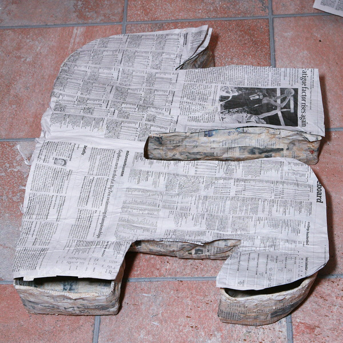 A pi shape is cut out from the sheet of flat paper mache, and placed on top of the main pi shape, as a cover.