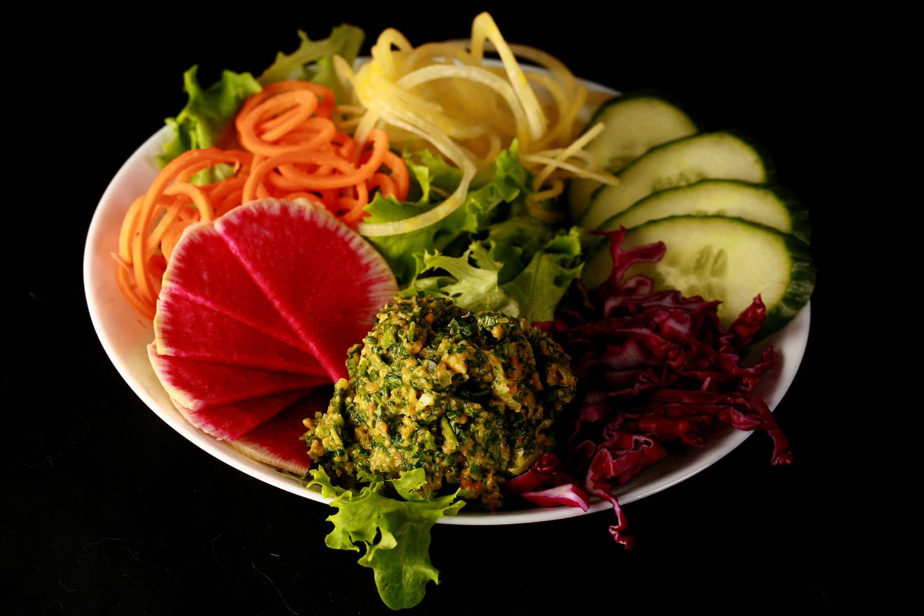 A large scoop of cilantro pesto is shown against the backdrop of a gloriously colourful salad - greens, watermelon radish, spiralized carrots and yellow beets, cucumber, and purple cabbage!
