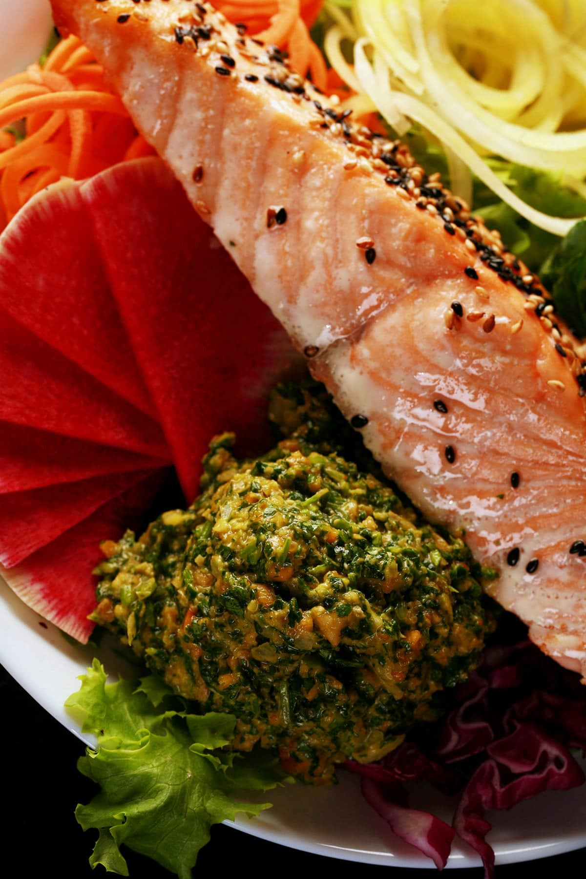 A large scoop of cilantro pesto is shown against the backdrop of a gloriously colourful salad - greens, watermelon radish, spiralized carrots and yellow beets, cucumber, and purple cabbage, with a slice of baked salmon on top!