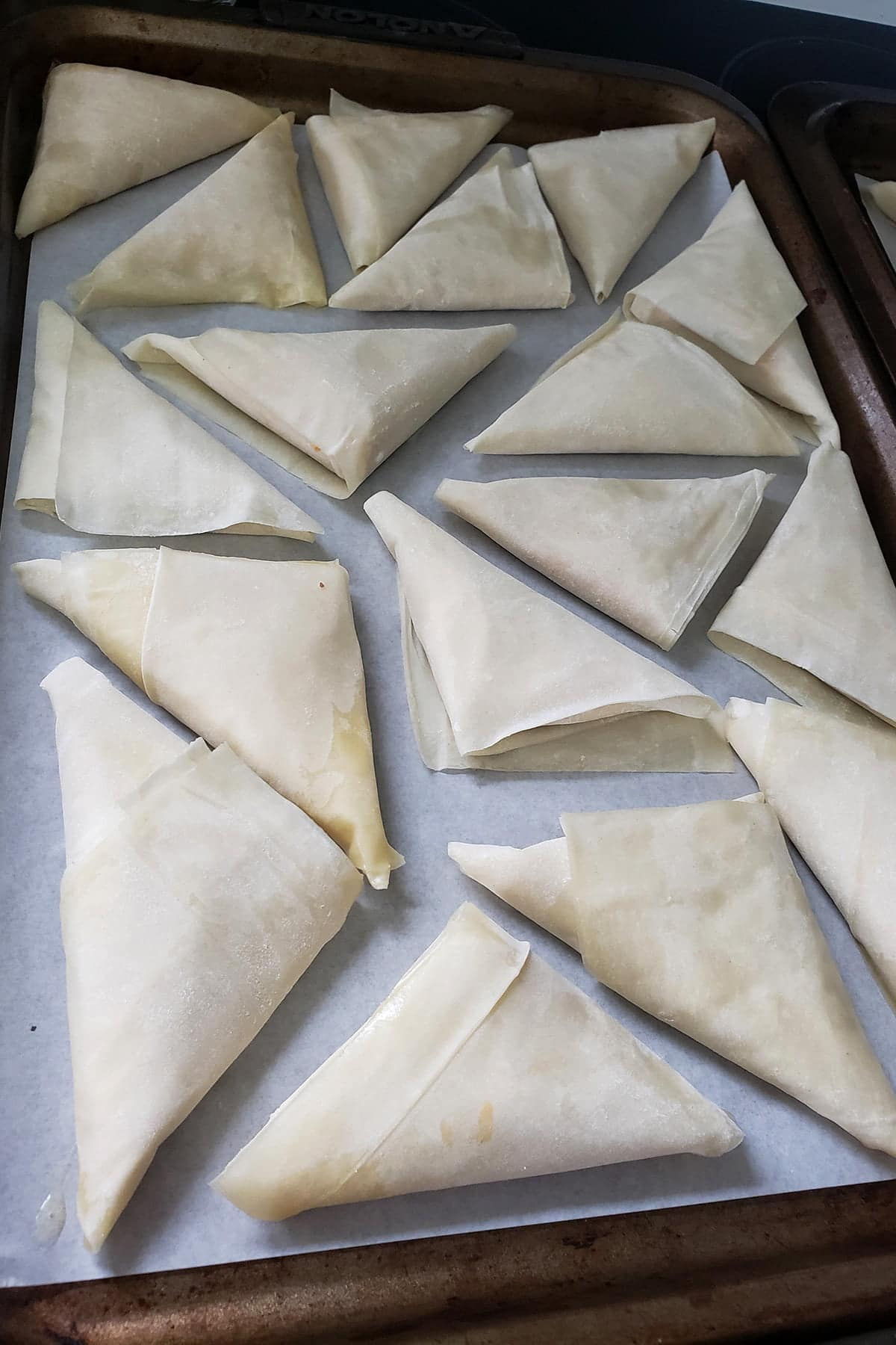 A baking sheet that is lined with parchment paper. About a dozen raw, trianglar pastries have been arranged on the pan, about to be baked.