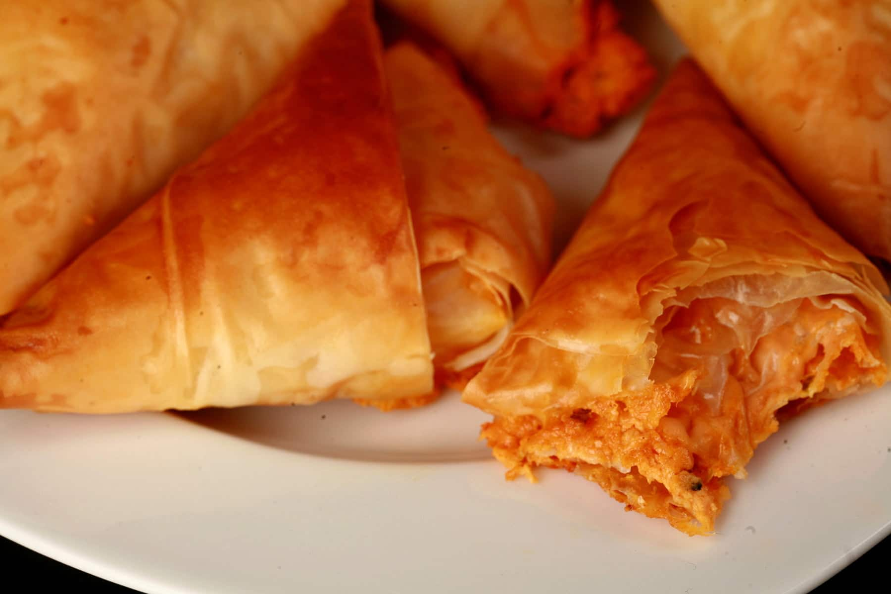 A close up view of crab triangles - a triangular pastry made from folded phyllo dough. They are flaky and crispy, with a red filling showing from one that has been bitten into.