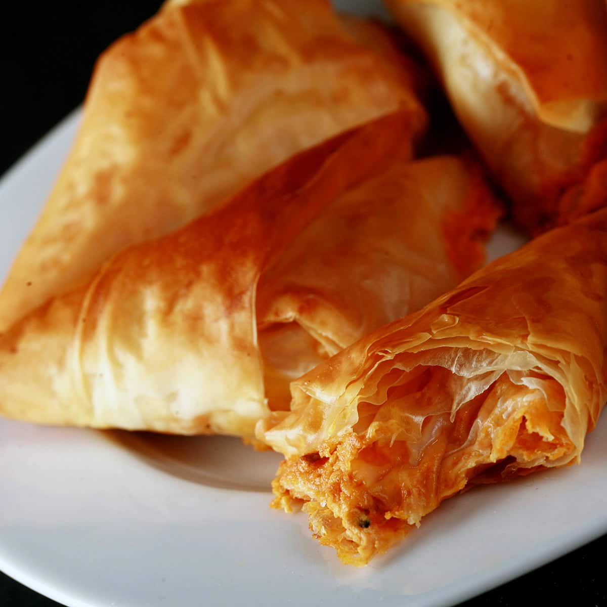 A close up view of a triangular pastry made from folded phyllo dough. They are flaky and crispy, with a red filling showing from one that has been bitten into.