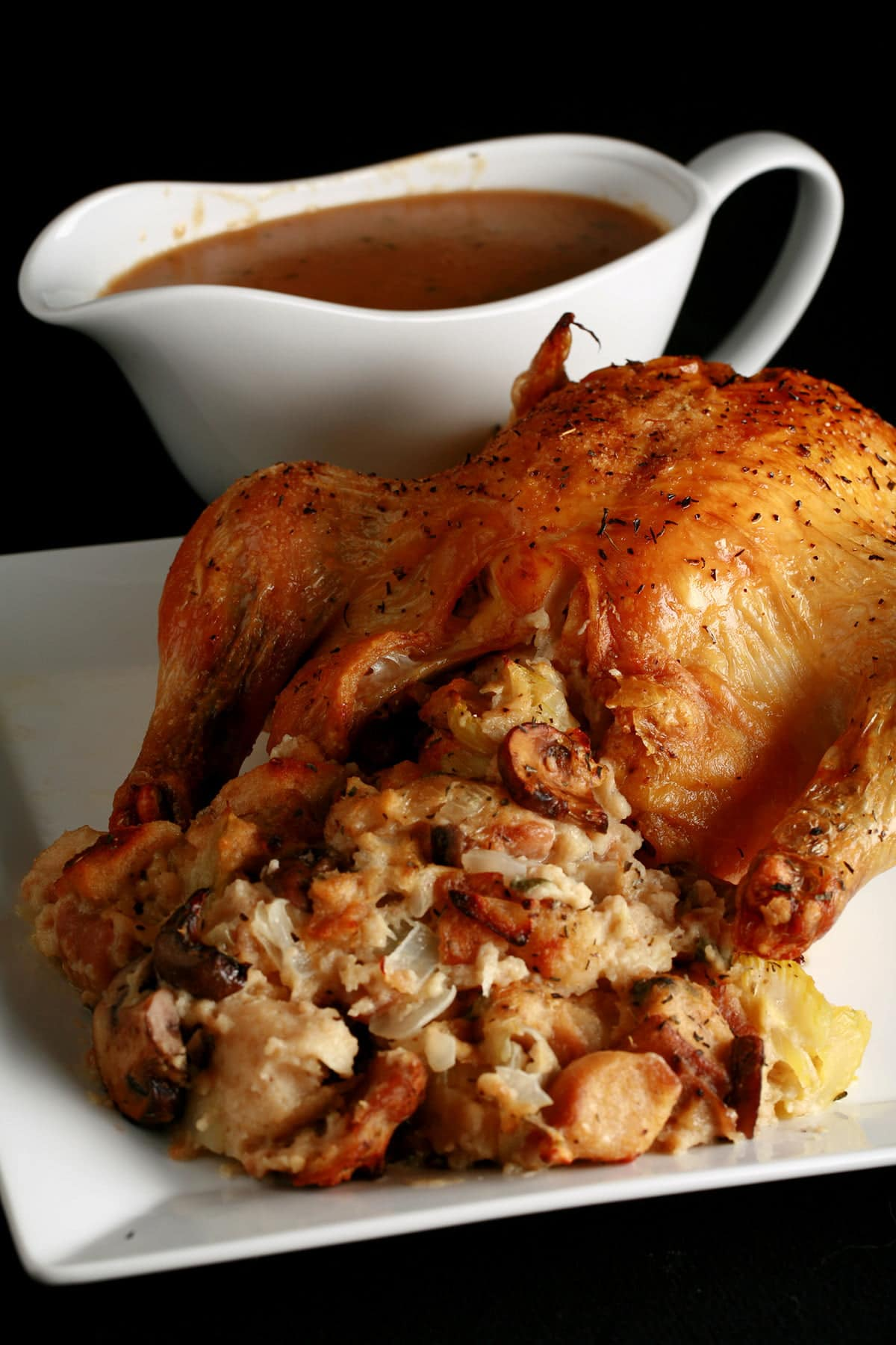 Close up image of a roasted turkey, with an abundance of stuffing visible. It is on a white plate, and there is a bowl of gravy next to it.