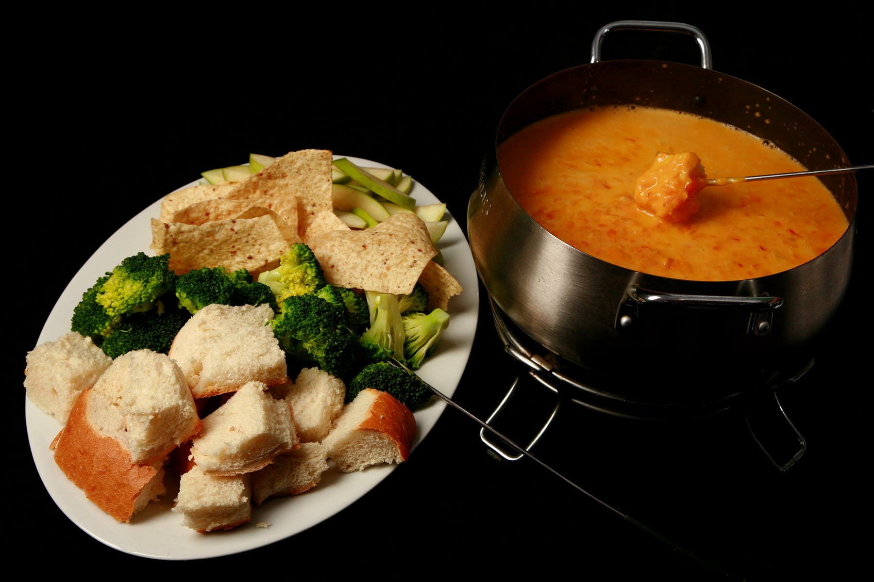 A large platter of bread cubes, broccoli, torilla chips, and apple slices. It's next to a metal fondue pot full of southwest fondue.