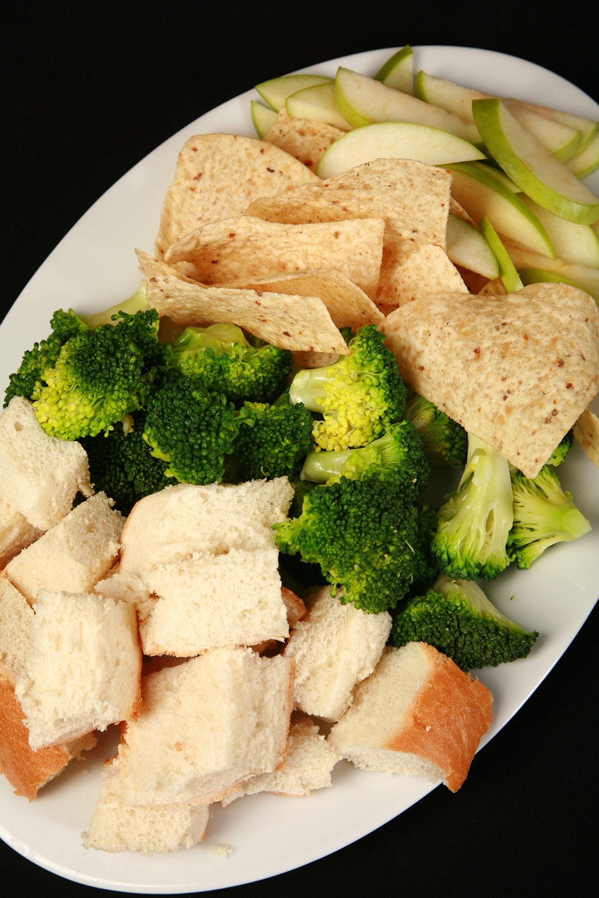 A large platter of bread cubes, broccoli, torilla chips, and apple slices.