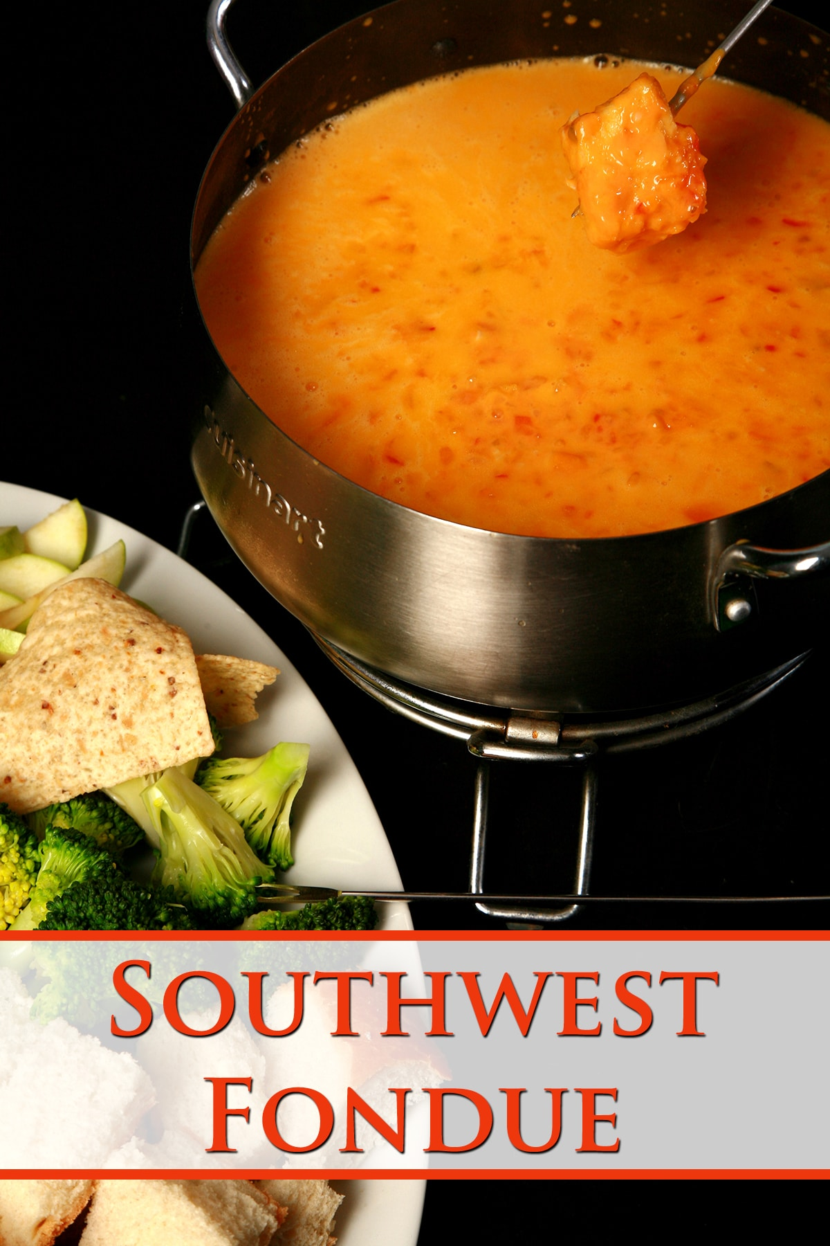 A fondue pot of southwest fondue, next to a plate of bread cubes, broccoli, and tortilla chips.