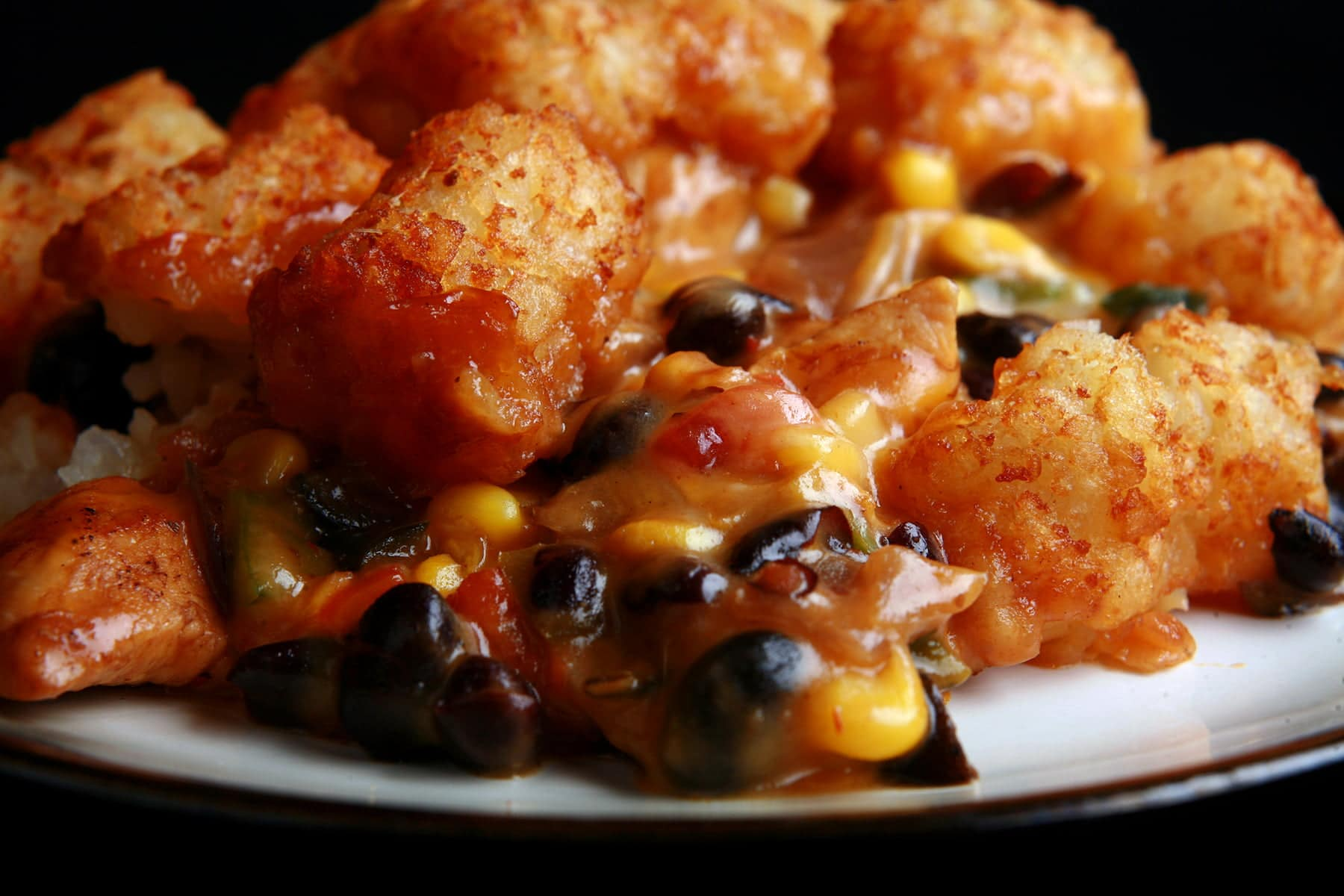 A close up view of a serving of southwest hot dish. Chicken, black beans, salsa, cheese sauce are visible, with crispy tater tots on top.