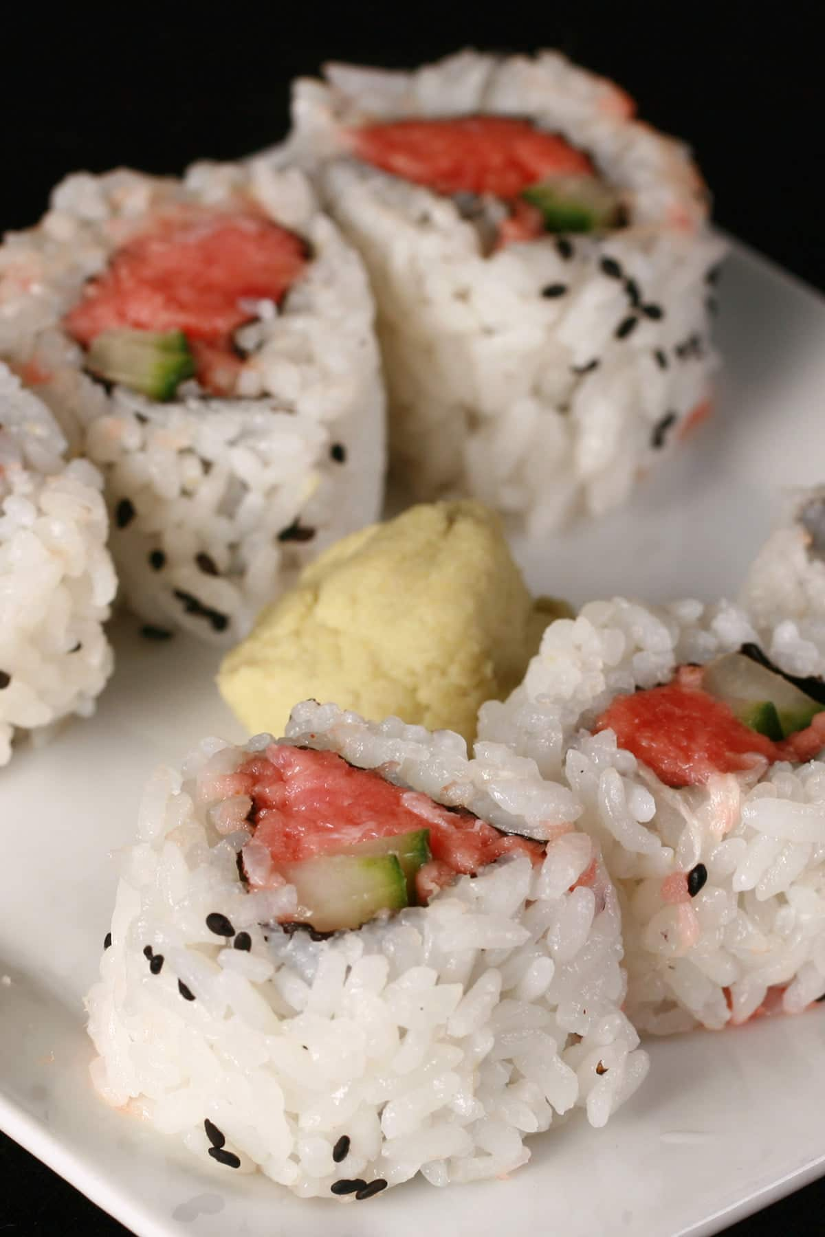6 pieces of spicy tuna maki are arranged on a white plate, with a glob of wasabi in the middle.