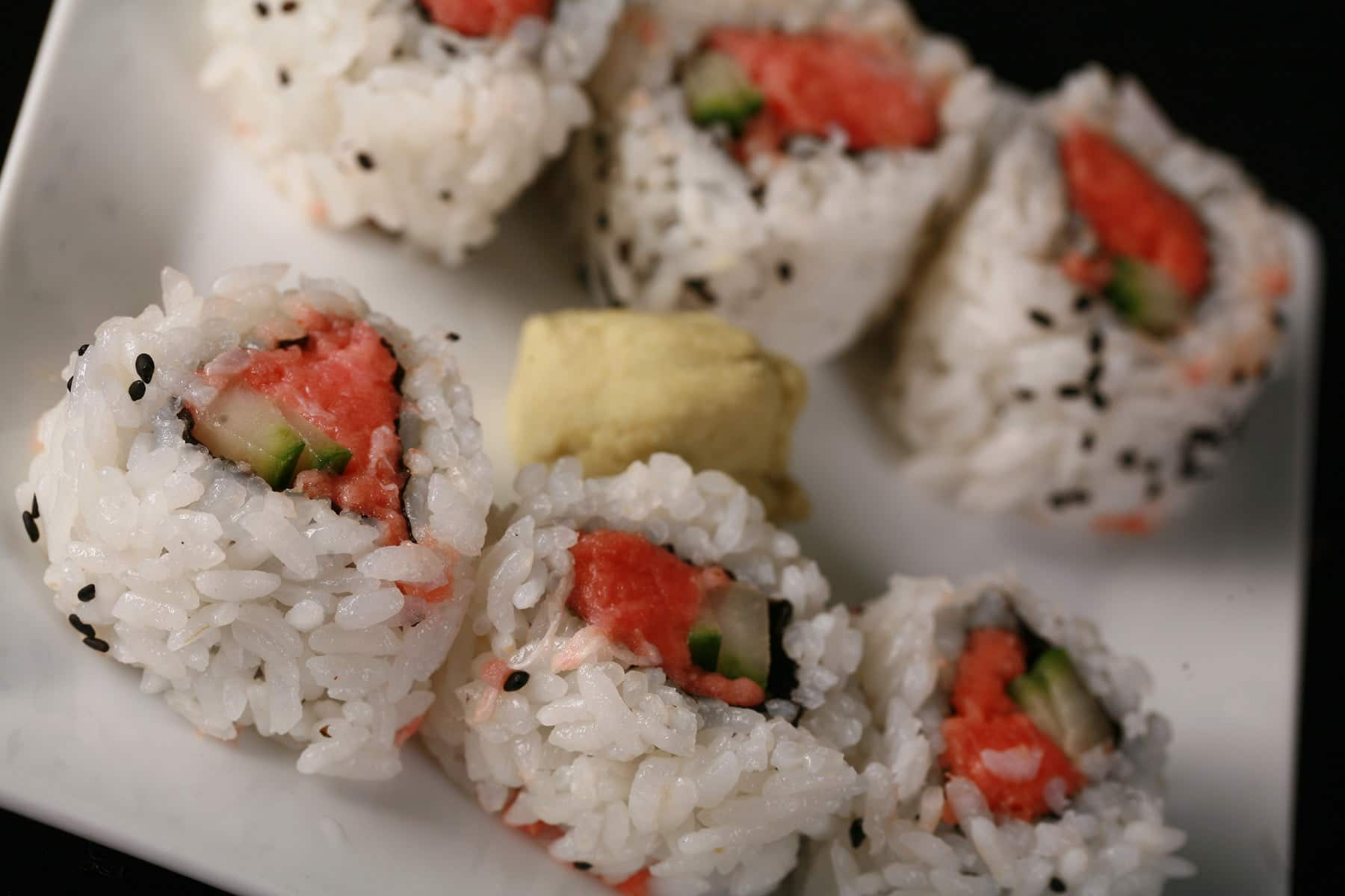 6 pieces of spicy tuna sushi roll are arranged on a white plate, with a glob of wasabi in the middle.