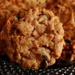 A small, faceted glass plate with several highly textured round cookies on top. Coconut, butterscotch chips, nuts, and raisins are visible throughout.