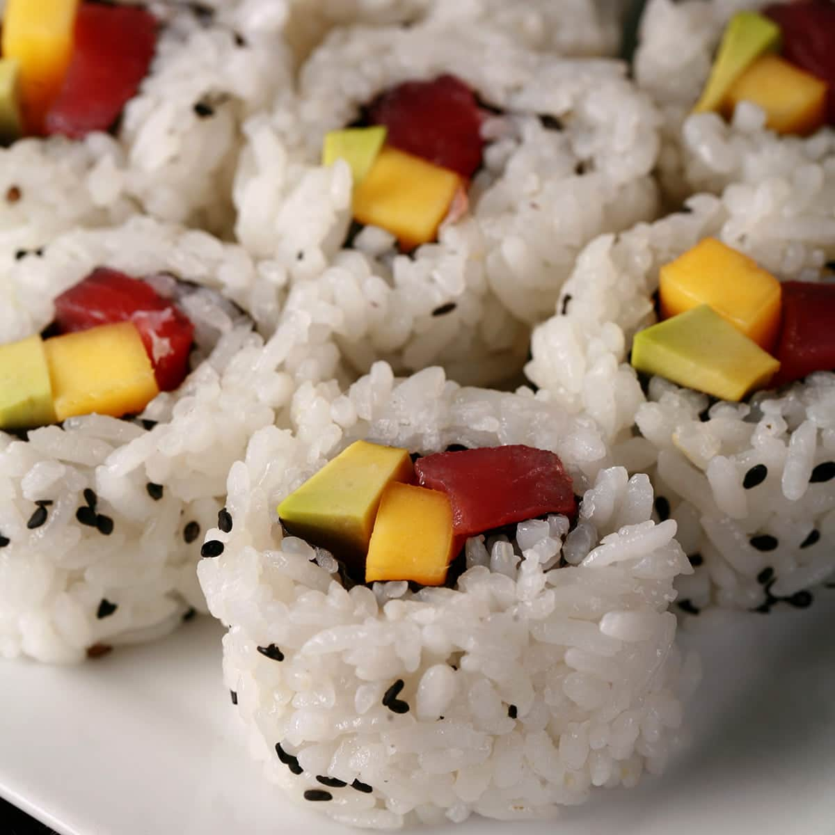 7 pieces of tuna avocado and mango sushi roll slices, on a small white plate.
