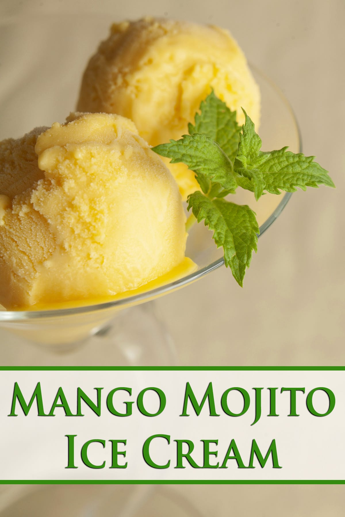 Two scoops of a rich yellow mango mojito ice cream, in a martini glass. It's garnished with a sprig of fresh mint.