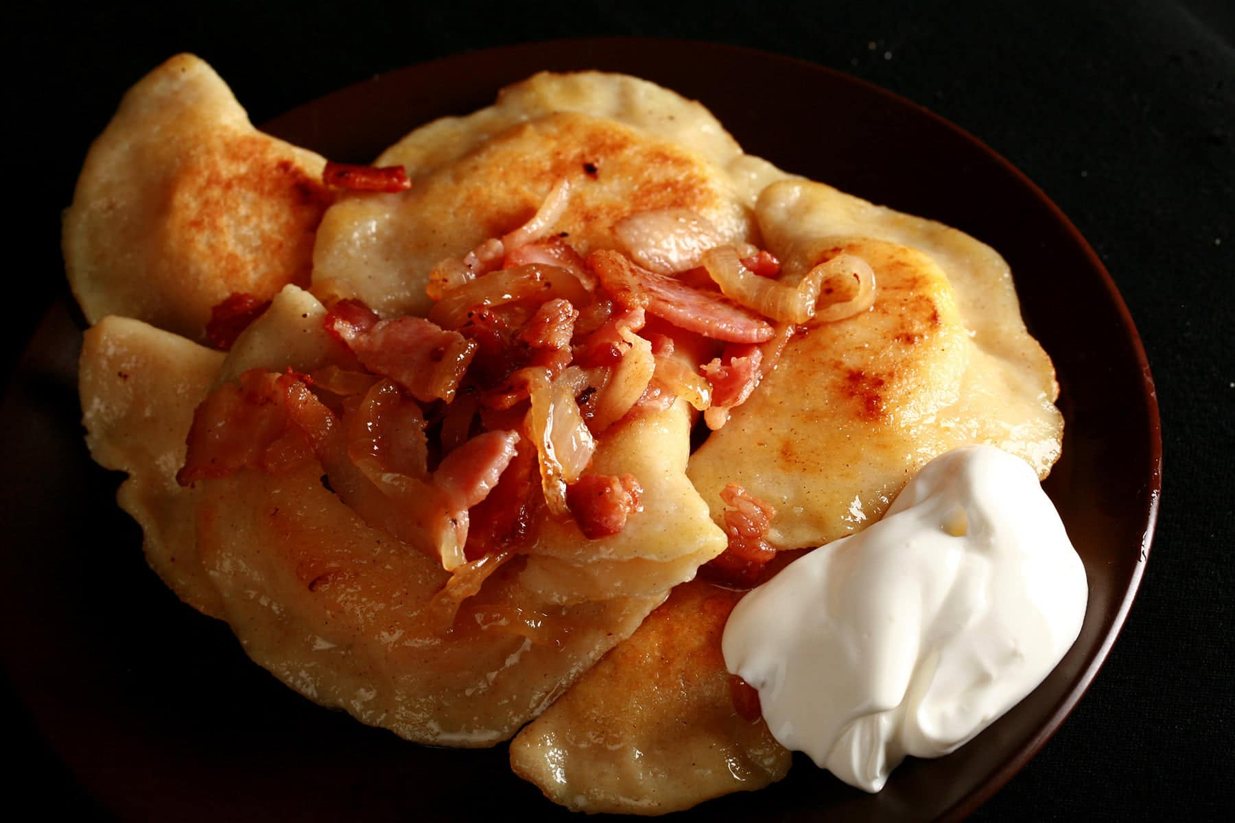 A plate of homemade pierogi - Ukrainian dumplings filled with cheesy potatoes. They are pictured with pieces of bacon on top, and a scoop of sour cream on the side.
