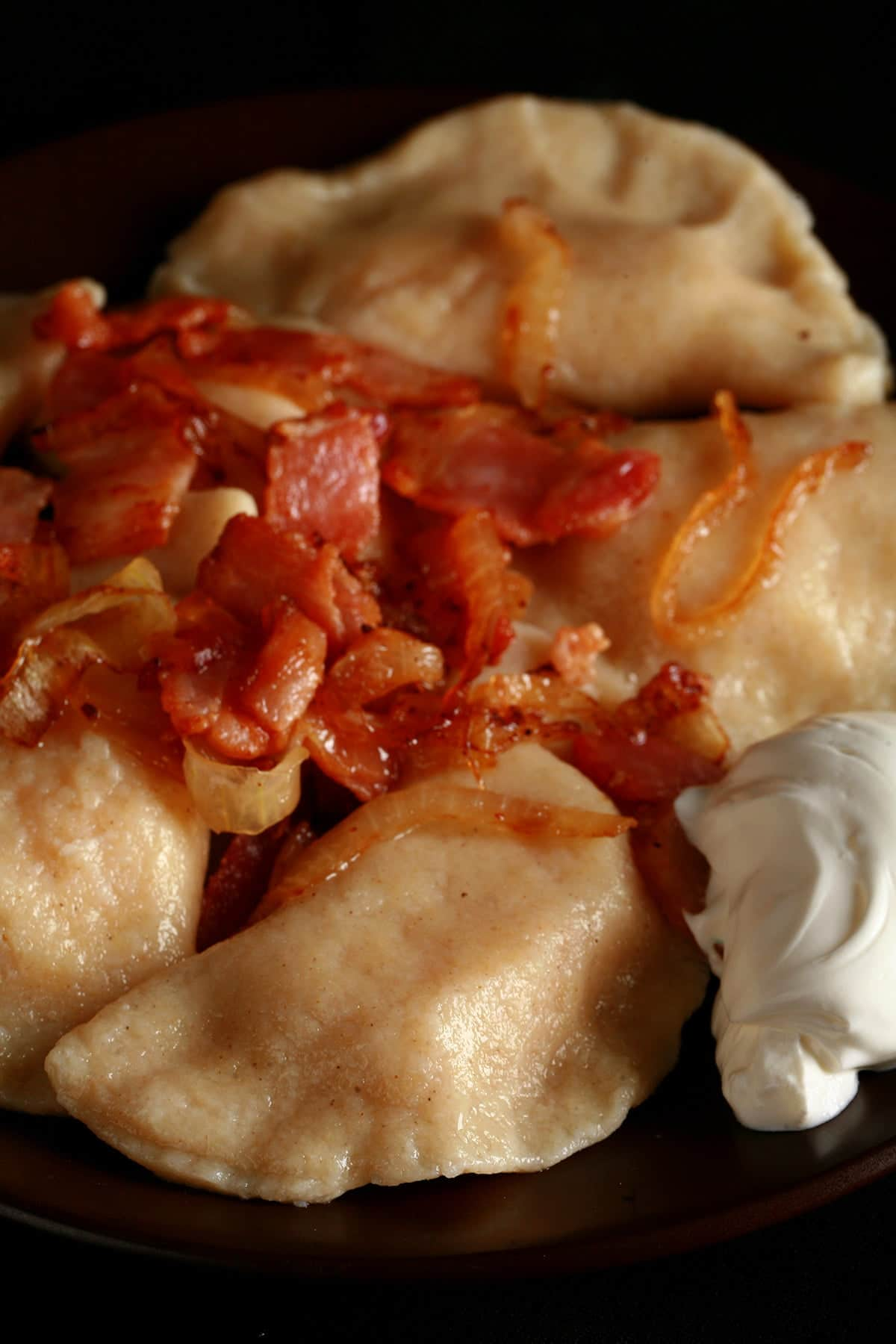 A plate of homemade perogies - Ukrainian dumplings filled with cheesy potatoes. They are pictured with pieces of bacon on top, and a scoop of sour cream on the side.