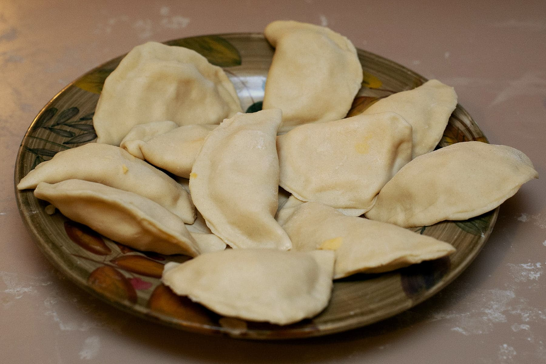 A large brown plate is loaded with homemade pierogi, waiting to go in the boiling water.