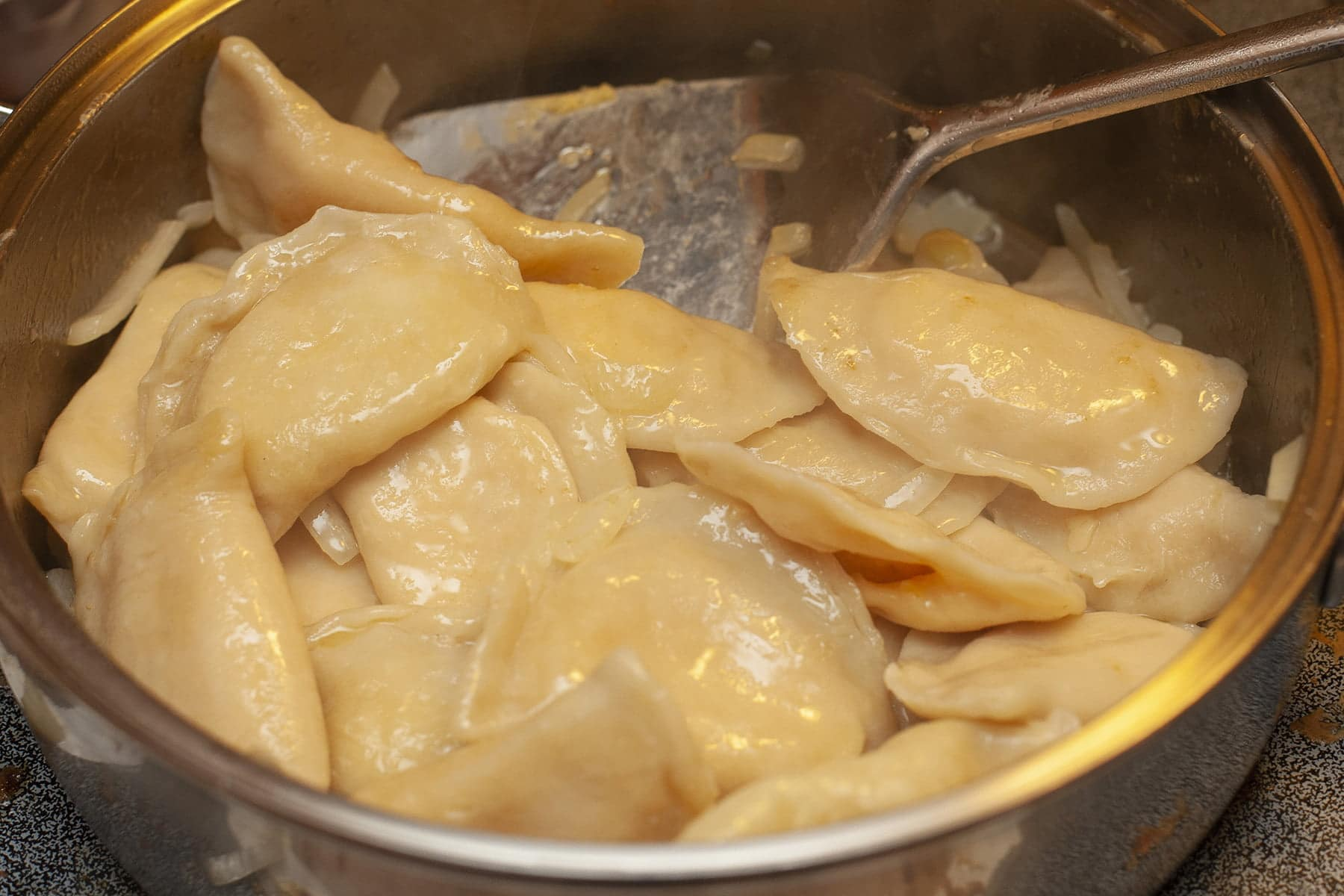 A large metal pan holds about a dozen perogies, being sauteed in butter.