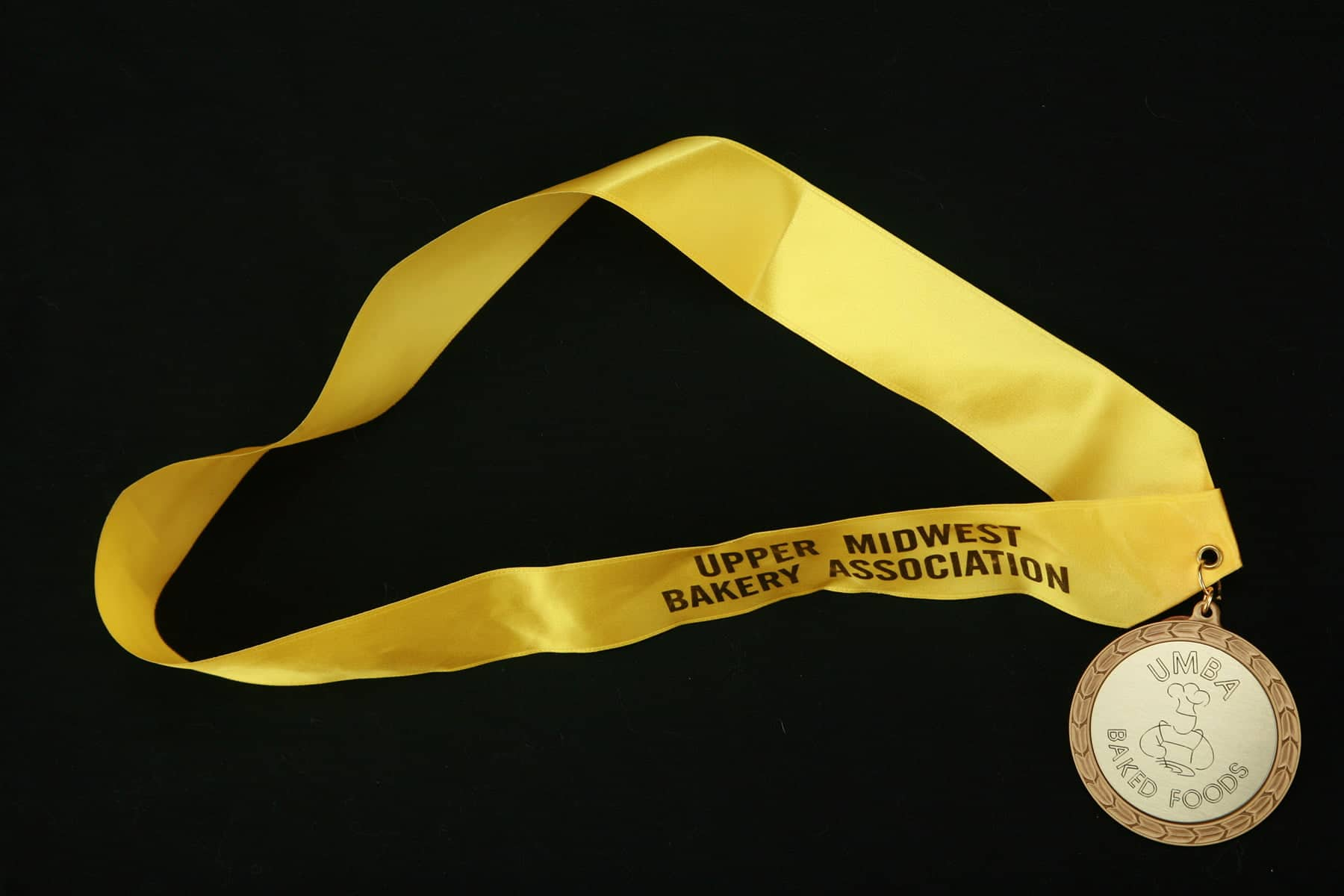 A competition gold medal with a bright yellow ribbon, against a black background.