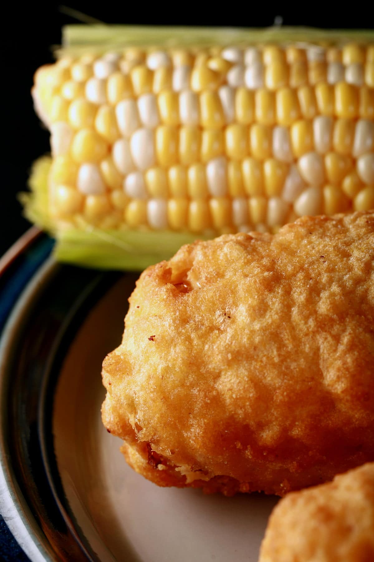 2 cobs of corn - 1 fresh, 1 battered and deep fried - are lined up on a plate.