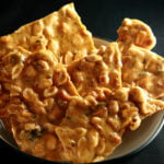 A close up view of jalapeno beer peanut brittle. It has green flecks of jalapeno pieces throughout.