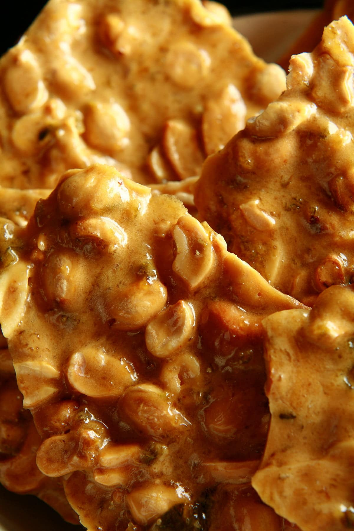 A close up view of peanut brittle with green flecks throughout - jalapeno pieces!