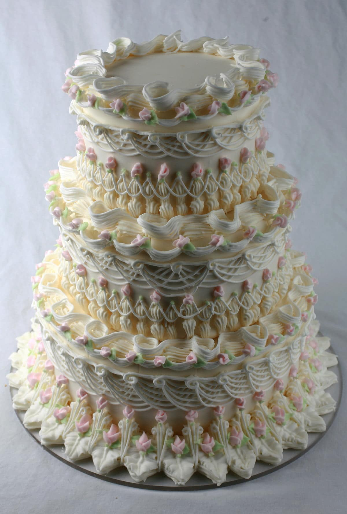 An ornately piped wedding cake, done in the lambeth style. Each layer is adorned with many layers of piping, overpiping, swags, scallops, and more. The cake is mostly white, with pale pink and green accents in the form of rosebuds.