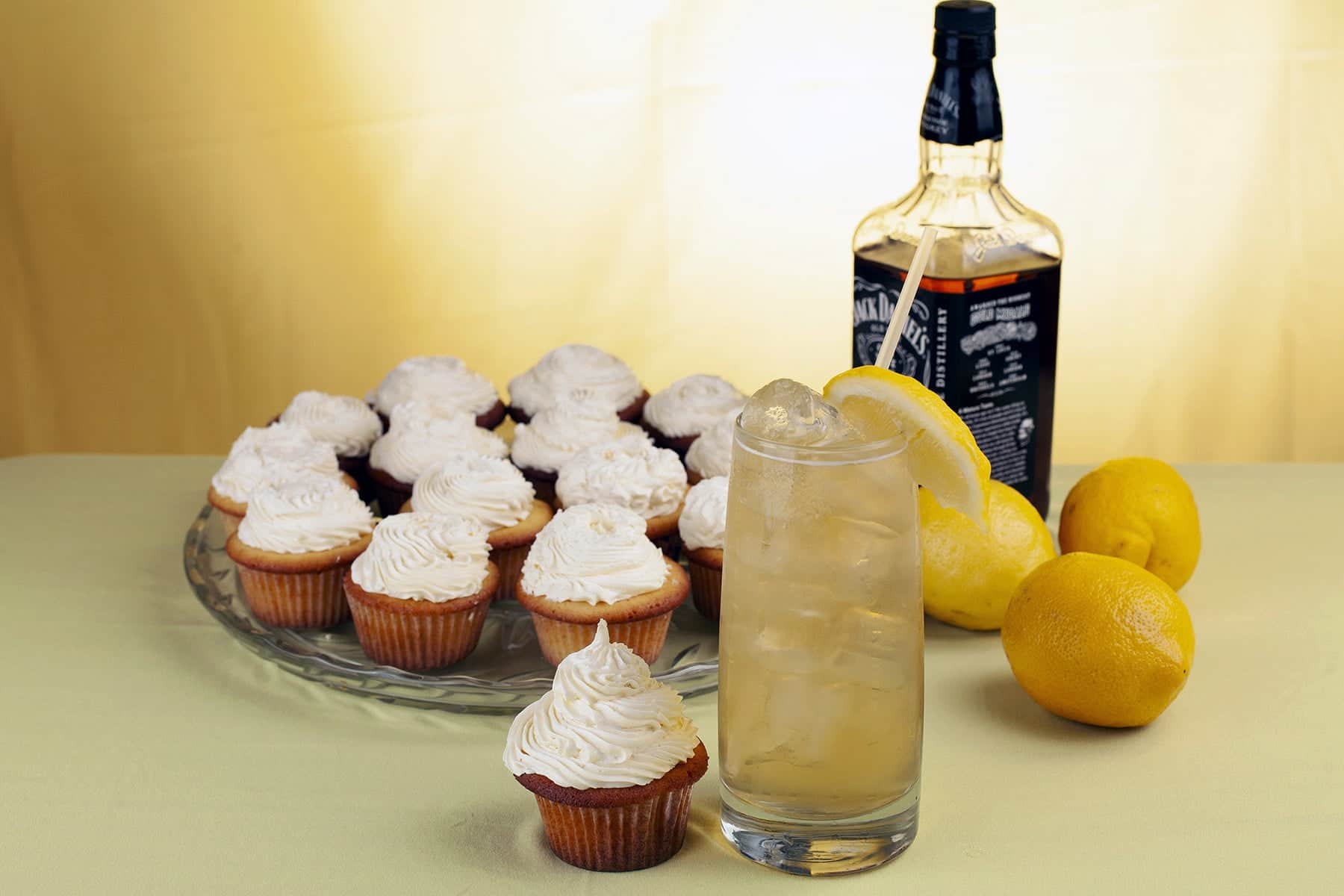 A tray of Lynchburg Lemonade Cupcakes is pictured with a bottle of Jack Daniels, a couple fresh lemons, and a glass of Lynchburg lemonade cocktail.