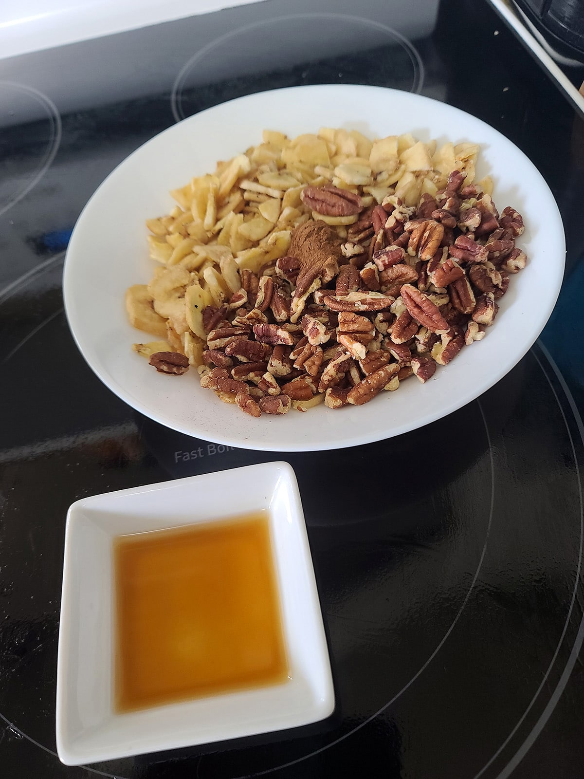A bowl of pecans, banana chips, and cinnamon,  next to a small bowl with the extracts measured into it.