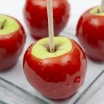 A square shaped glass plate with 4 Candy Apples on it. The apples are green - Granny Smith - and the candy dip on them is a bright shiny red.
