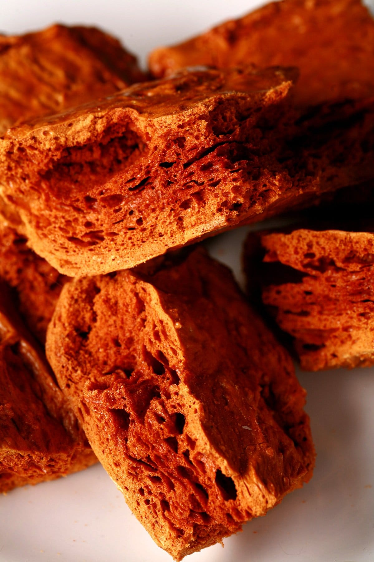 Chunks of deep amber coloured ginger-molasses sponge toffee are piled on a small white plate.