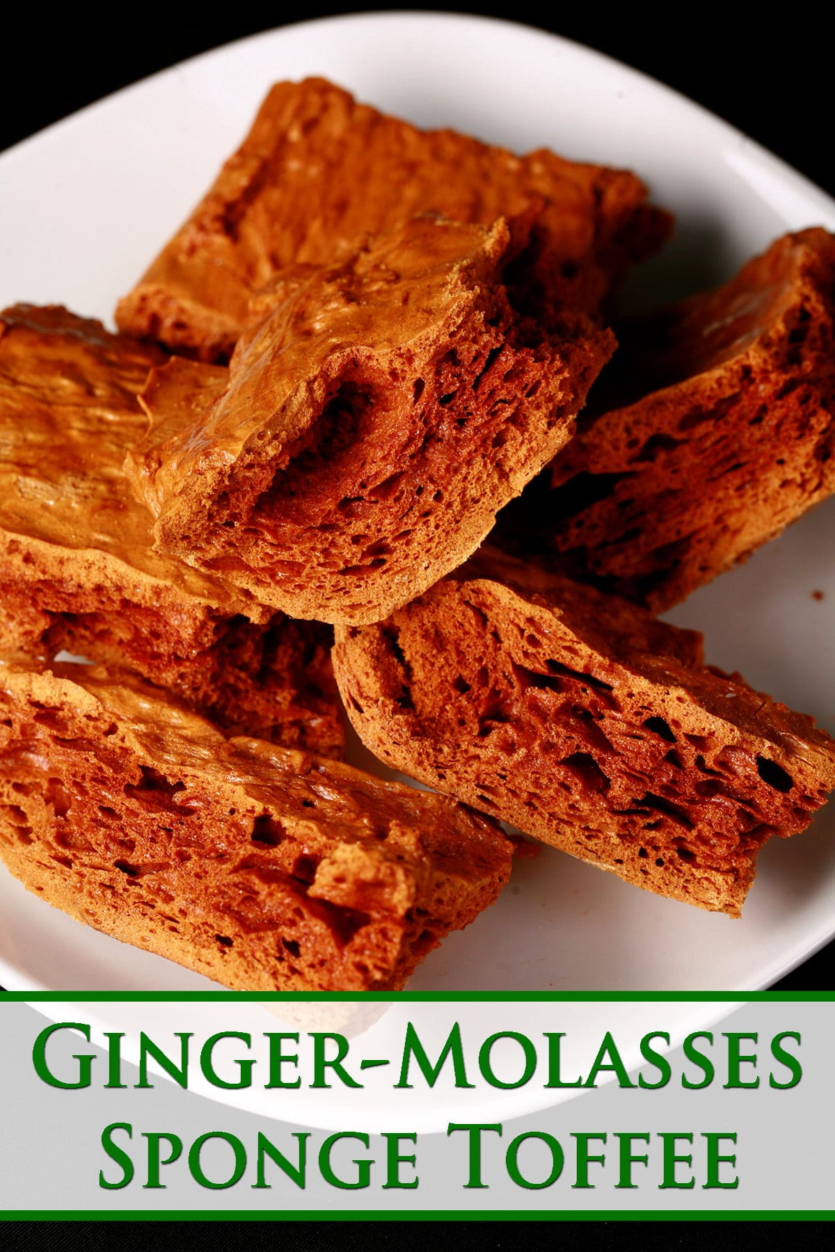 Chunks of deep amber coloured sponge toffee are piled on a small white plate.