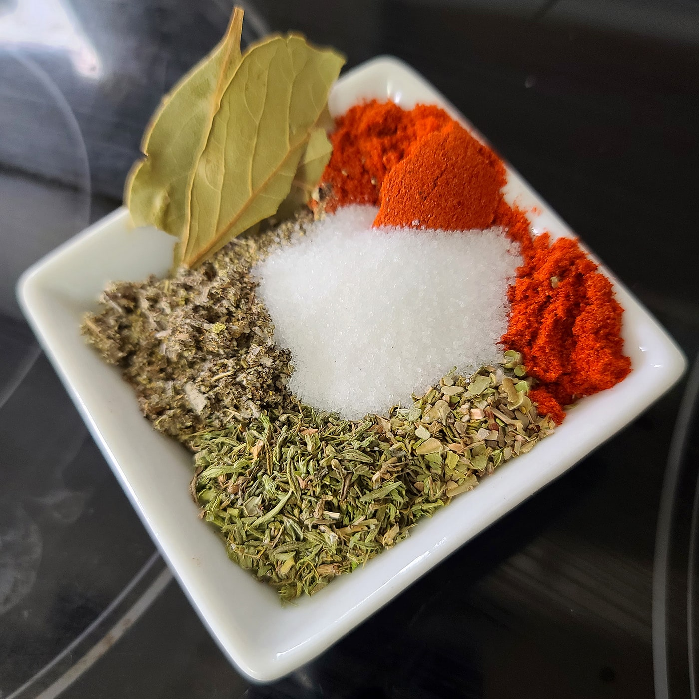 A small white bowl with the spices and bay leaves in it.