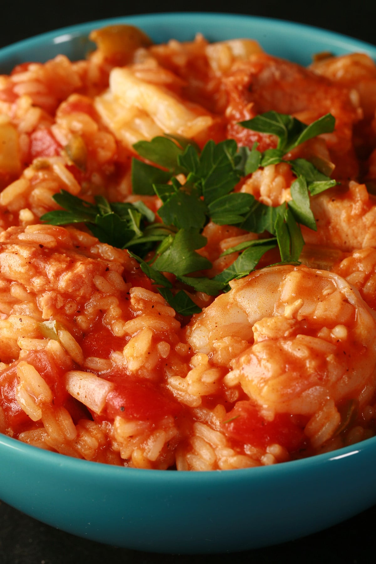 Chicken, shrimp, and sausage jambalaya, in a blue bowl. It is topped with chopped parsley.